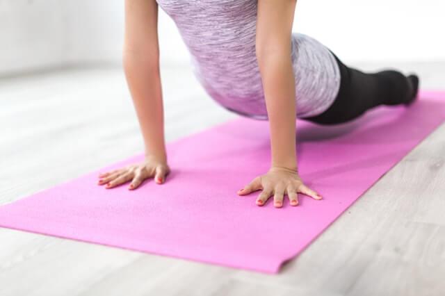 woman on pink yoga mat doing yoga