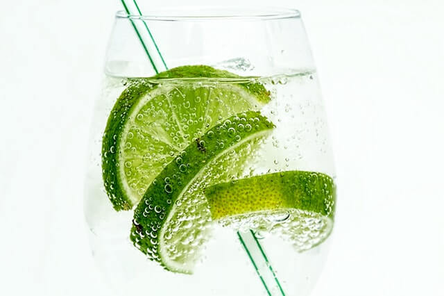 a glass of water with lime and a straw