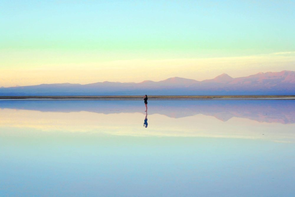 how to be honest with yourself and lady looking at reflection in the ocean with mountains in the background