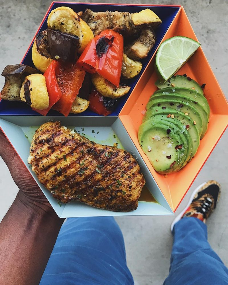 a man holding chicken, avocado, and vegetables