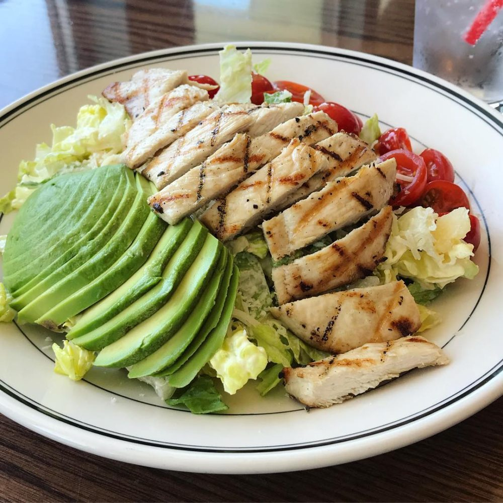 a plate of chicken, avocado, tomato and salad