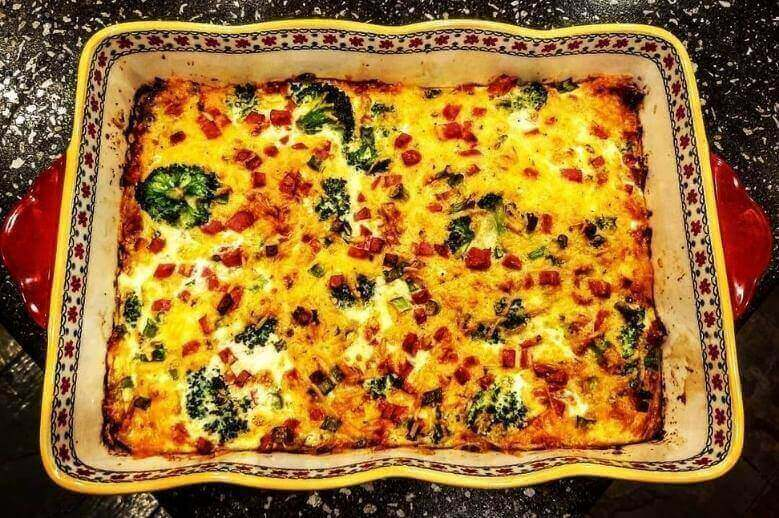a low-carb broccoli, ham, and eggs breakfast casserole in a floral casserole dish