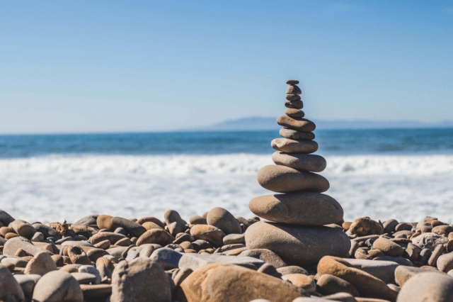 wellness rocks stacked at the ocean on a sunny day