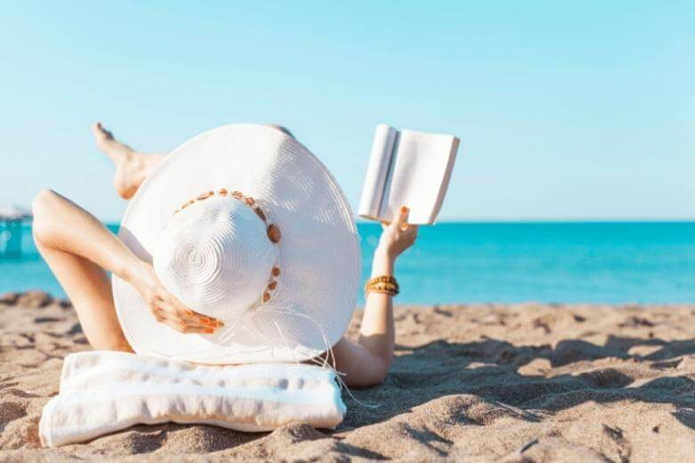 empath traits / woman reading on the beach