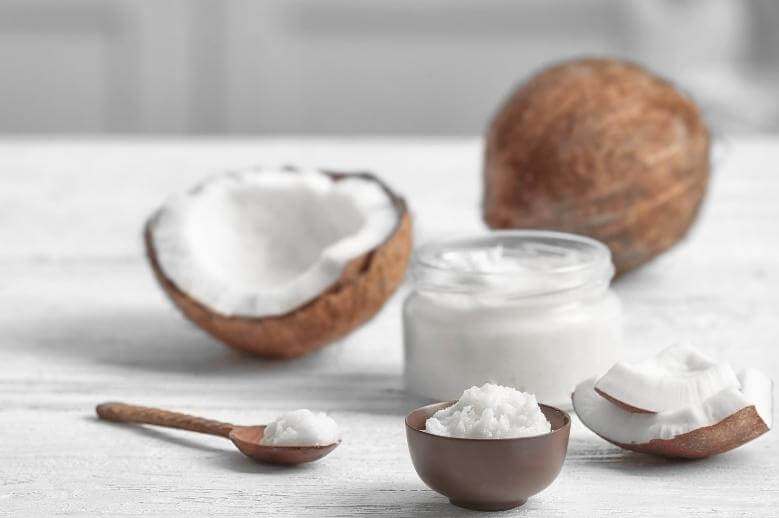 8 coconut oil benefits / a coconut, a glass jar full of coconut oil, a wooden spoon on a white wooden table