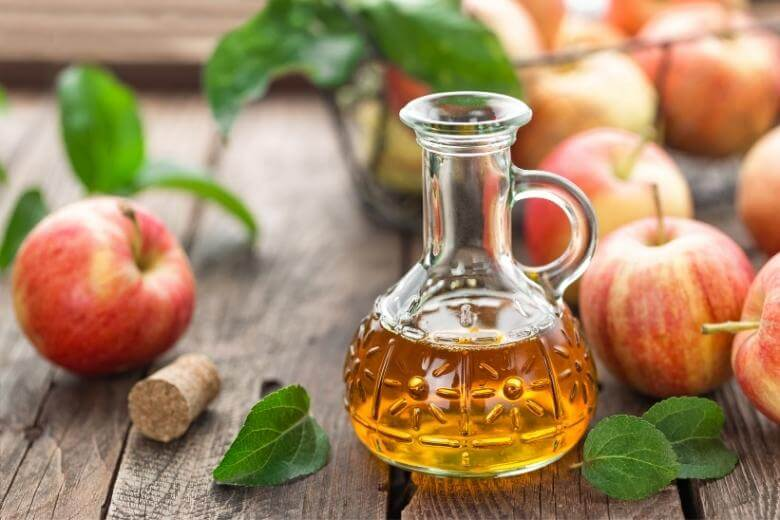 health benefits of apple cider vinegar / ACV and apples on a table