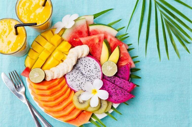 healthy tropical fruit on a plate with a fruit smoothie