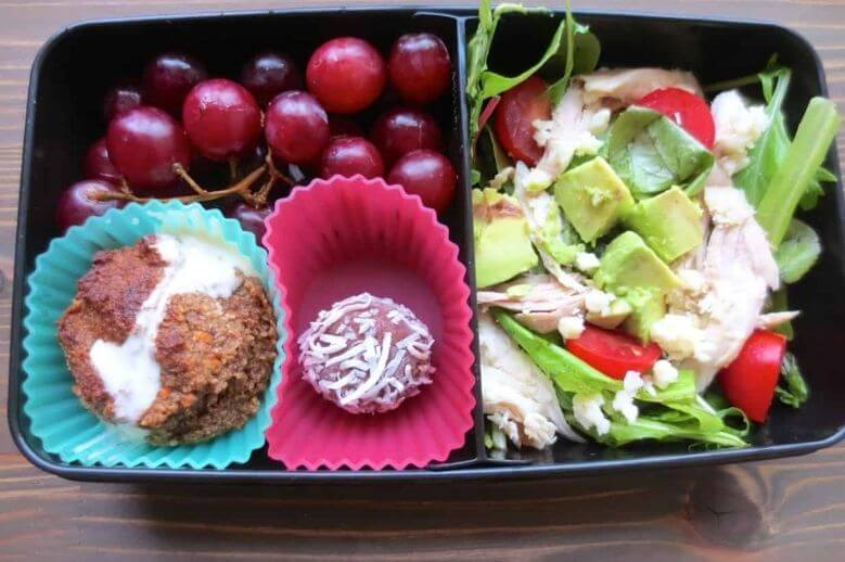 healthy lunch ideas bento box lunch with grapes, salad, chicken, avocado, carrot muffin, and coconut bite