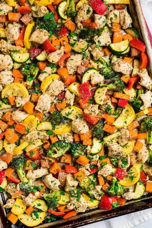 chicken with squash, herbs, and peppers on pan