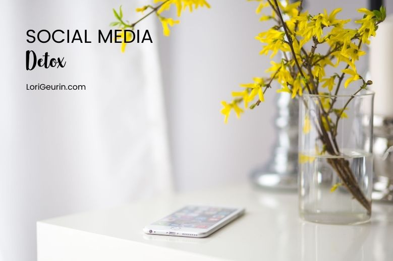cellphone setting on table next to vase of yellow flowers