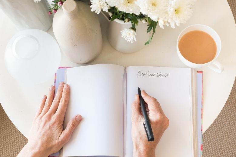 woman writing in a gratitude journal and a cup of coffee and flowers