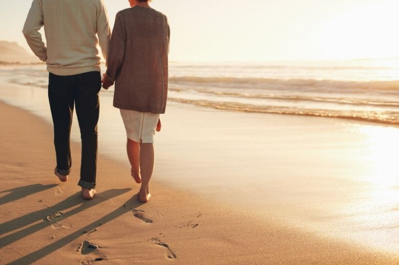 a couple walking on the beach holding hands grateful for their love