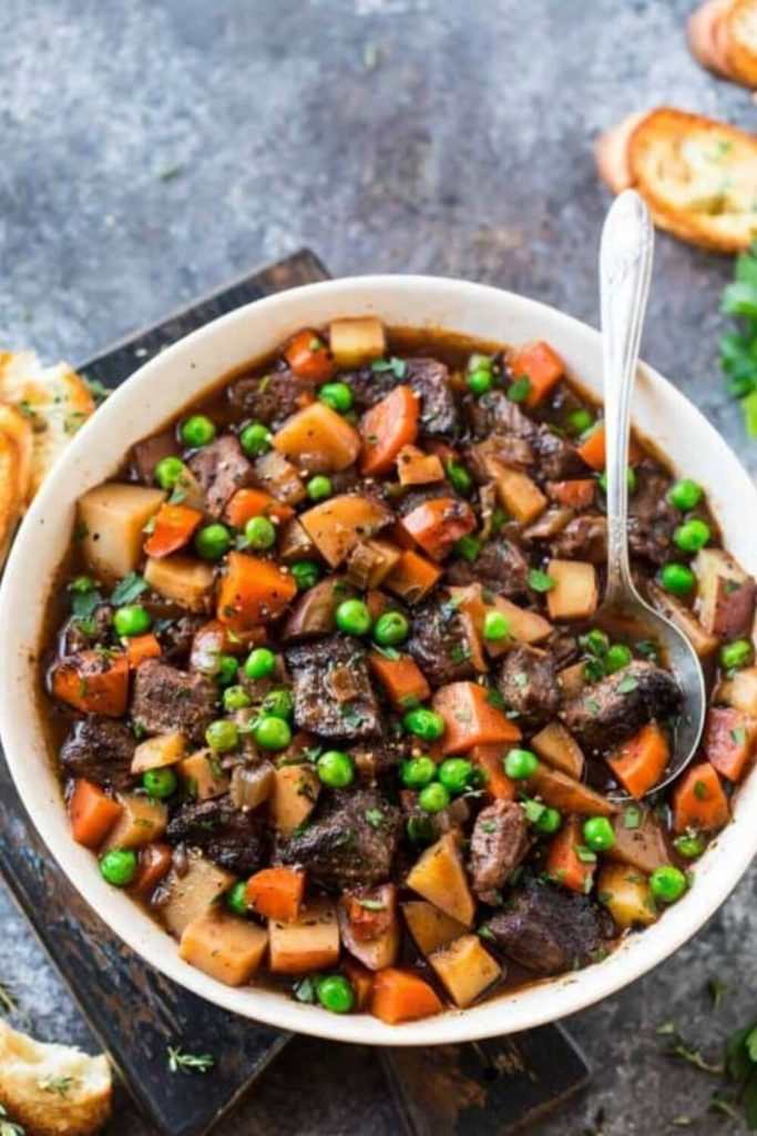 crockpot beef stew in a white bowl with bread