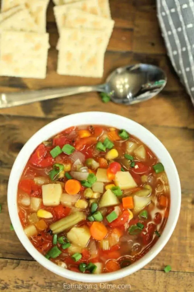 vegetable soup with crackers and a spoon on a wooden table