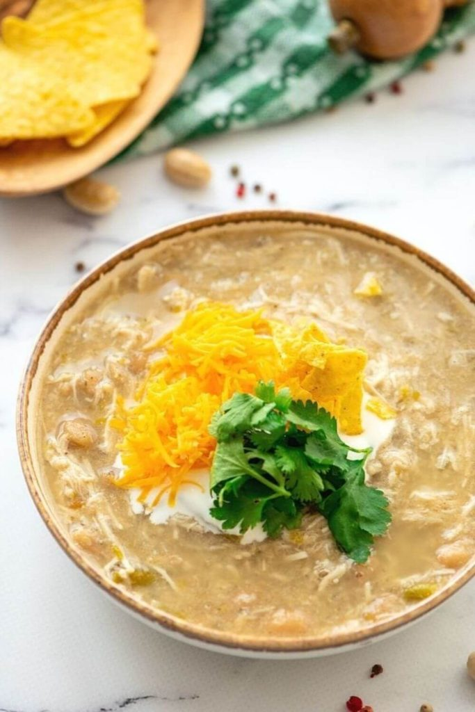crockpot white chicken chili topped with sour cream and cheese in a bowl