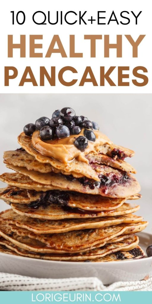 a big stack of healthy pancakes topped with peanut butter, blueberries, and maple syrup on a white plate