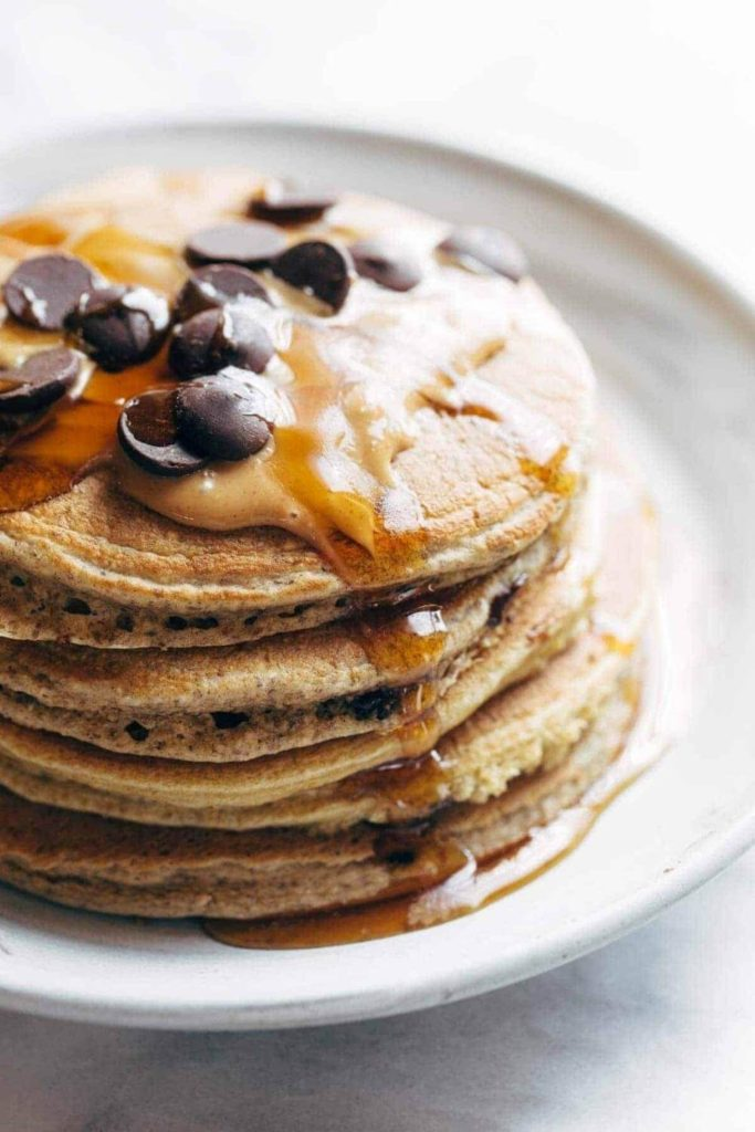 a stack of pancakes with peanut butter, chocolate chips and maple syrup on a white plate