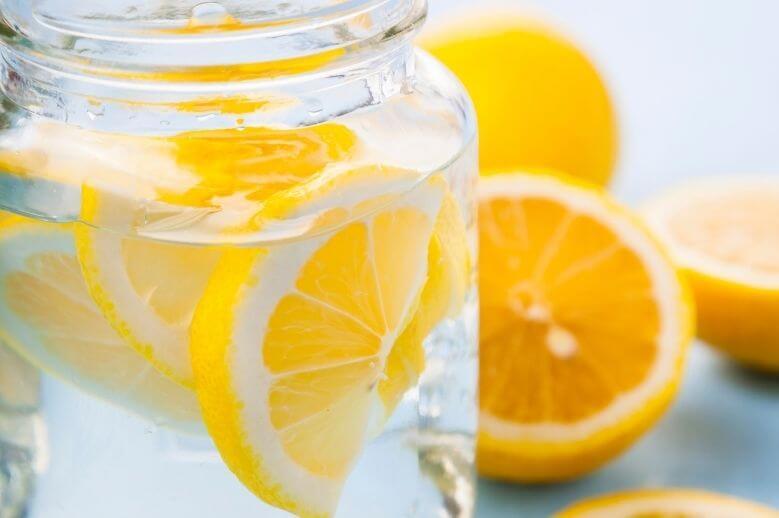 lemon water in a big glass jar with lemons