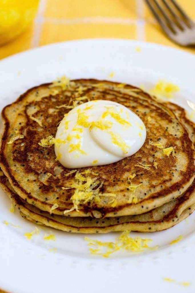 lemon poppy seed pancakes topped with yogurt and lemon peel on a white plate