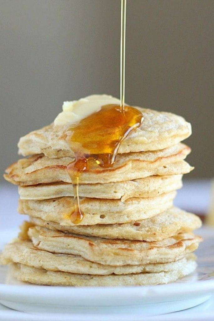 healthy oatmeal pancakes with syrup and butter on a white plate