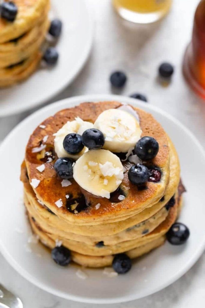healthy blueberry pancakes with bananas, coconut, and syrup on a white plate on a table