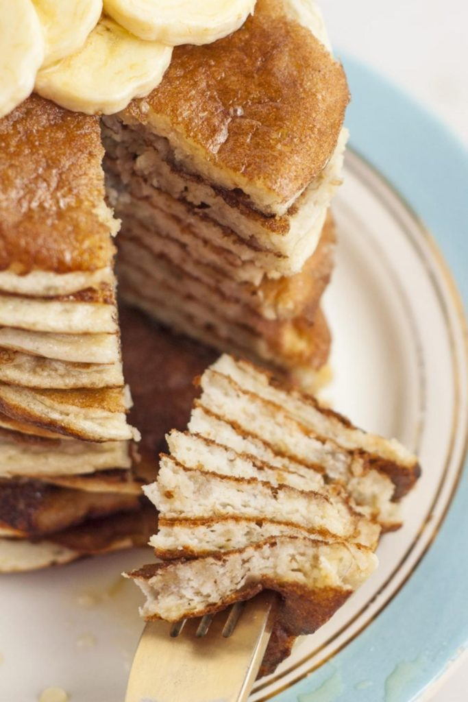 5 ingredient pancakes in a huge stack, sliced,  with a big bite on a fork