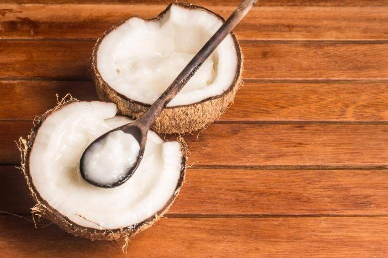 coconut halves with coconut oil on a wooden table