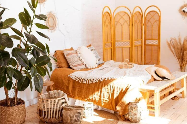 boho bedroom with pillows, blankets, and plants